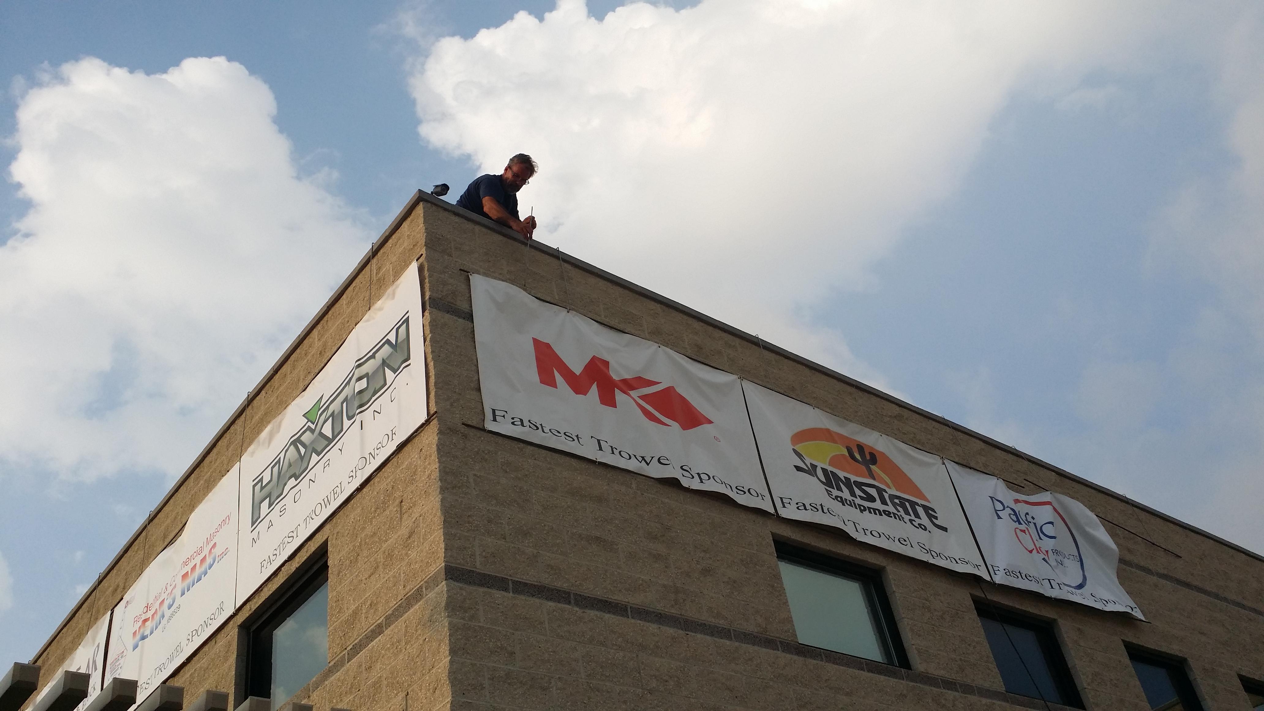 Mike Baumgarten hangs from the rooftop
