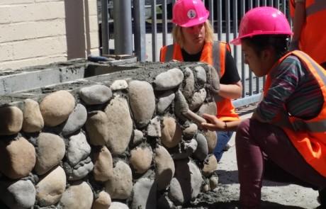 Girl mason brushing rocks on wall